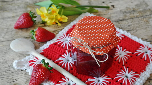 strawberry jam in clear bottle with three strawberry fruits beside
