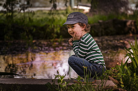 selective focus photo of a boy squatting near body of water