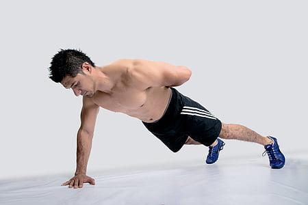 man wearing black Adidas shorts and blue shoes executing push-up with one hand