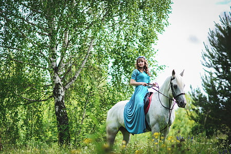woman in blue dress riding on white horse
