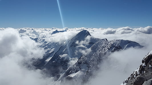 photo of foggy and snowcovered mountain