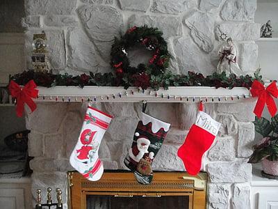 three Christmas socks hanging on fireplace
