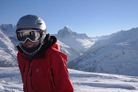 man wearing jacket standing on snowfield wearing helmet and goggles