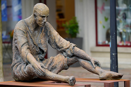 man sitting on brown bench statuette