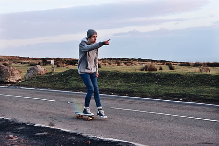 man riding skateboard in the middle of road