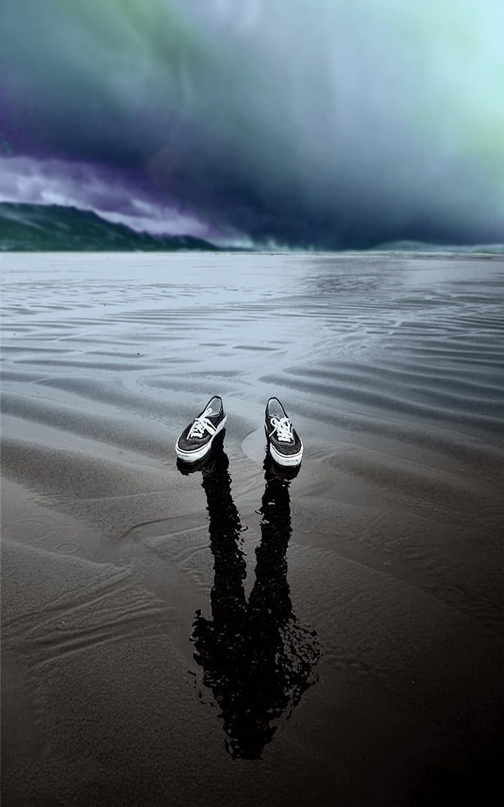 Pair of black and white sneakers floating on body of water