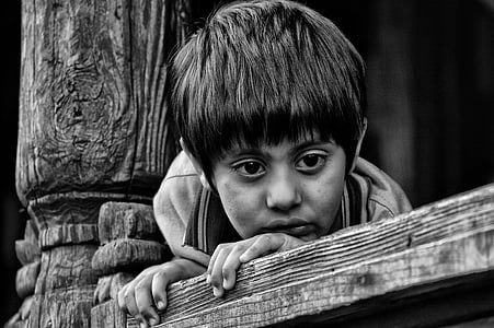 boy holding on brown wooden plank in black in white photography