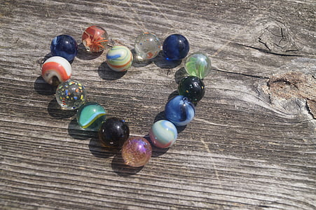 assorted toy marbles on beige wooden surface