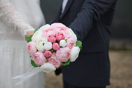bride and groom holding pink and white flower bouquet