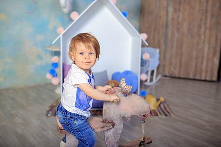 toddler wearing white and blue riding brown animal toy