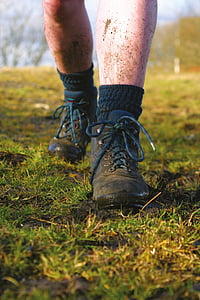 man wearing black leather boots standing on mud at daytime