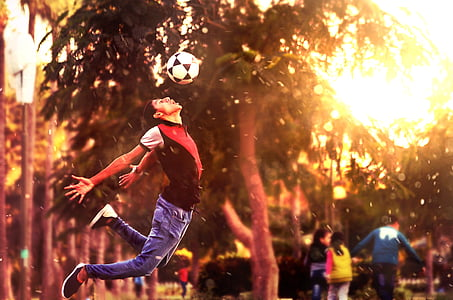 person playing soccer during sunset