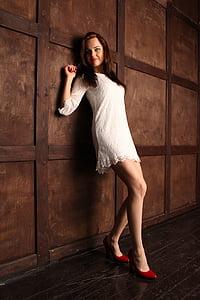 woman in white lace dress beside wall