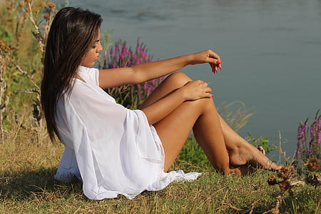 woman in white sitting on grass near body of water