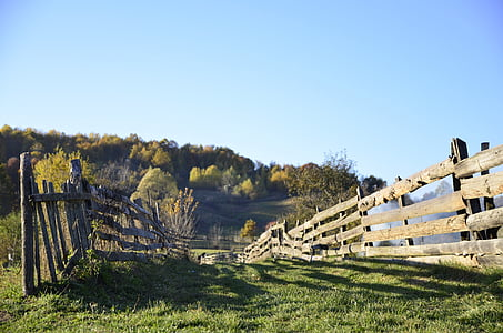 brown wooden fences on grass field under clear skies