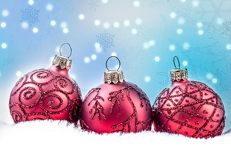 three Christmas baubles on white rug