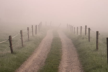 landscape photo of dirt road with brown wood posts by the road under foggy sky