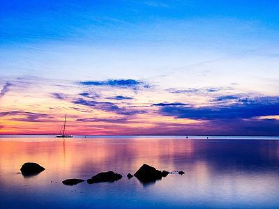 silhouette photo of boat and rock in calm body of water at sunset