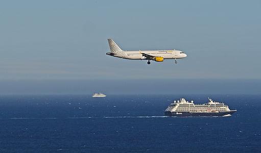 white airliner above ocean near cruise ship