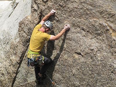 man wearing yellow shirt climbing on rock