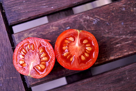 two slice tomato on brown wooden surface