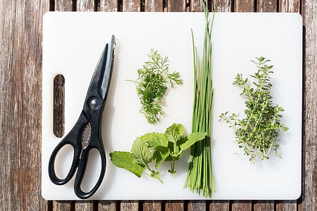 flat lay photography of black handled shears and four spices on white chopping board