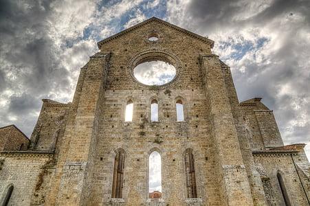 brown brick cathedral wall under cloudy skies