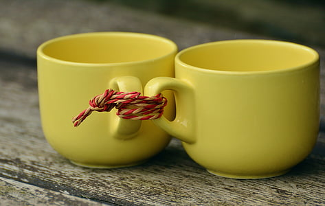 two yellow ceramic teacups tied together