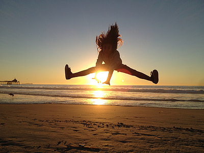 girl jumps on seashore during sunset
