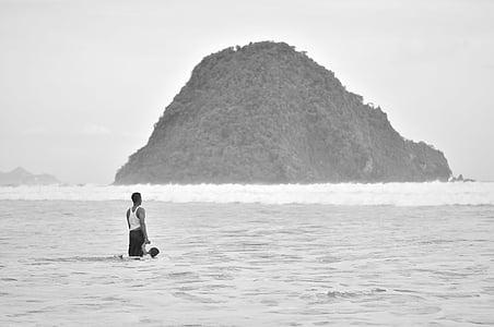 man standing on seashore near island