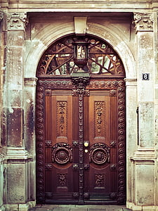 brown wooden embossed doors in a concrete building