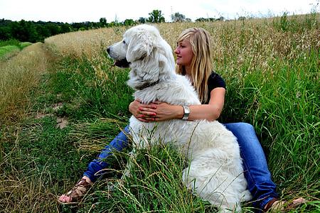 woman wearing black shirt hugging dog while sitting on grasses