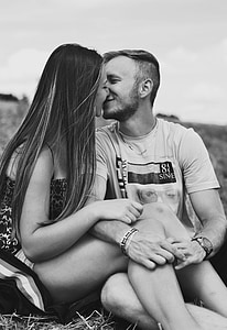 grayscale photo of couple kissing while sitting on grasses