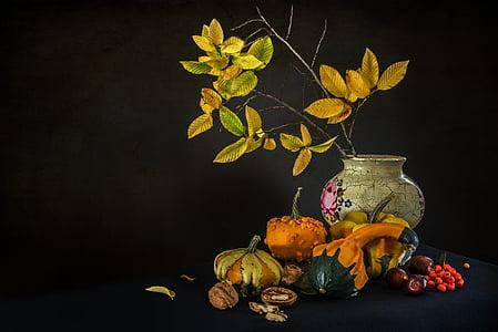 white ceramic vase beside pumpkins