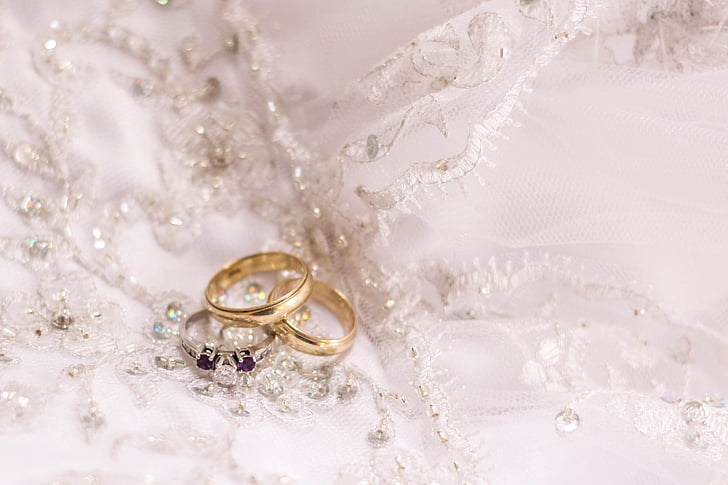 two gold-colored and one silver-colored rings