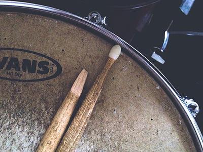 brown drumsticks on brown Vans snare drum