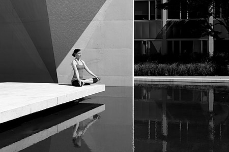 grayscale photo of woman in lotus position