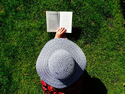 person wearing gray sun hat holding book