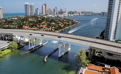 white yacht maneuvering under gray concrete bridge under daytime