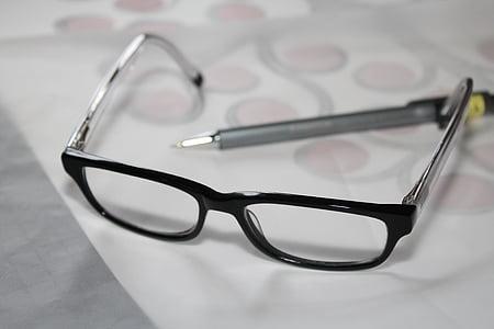 black framed eyeglasses near gray pen on white printer paper