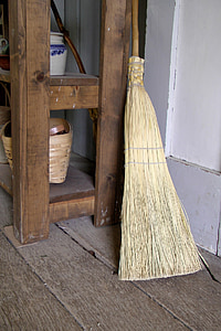 brown and beige broom leaning on table