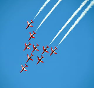 red-and-white jet planes in the sky and emitting white smoke
