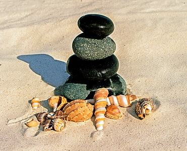stone stack and shell on sand