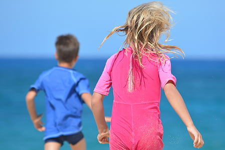 selective focus photo of girl and boy on seashore