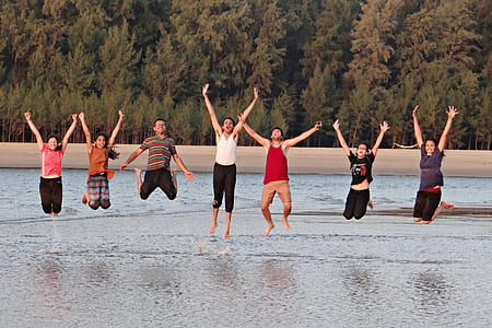 group of people jumpshot on the body of water