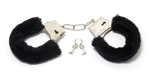 closeup photo of black and silver handcuffs with keys