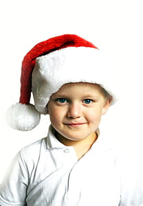 boy in white polo shirt and red Santa cap
