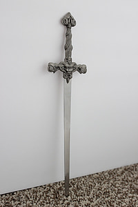 grey stainless steel sword near white concrete wall