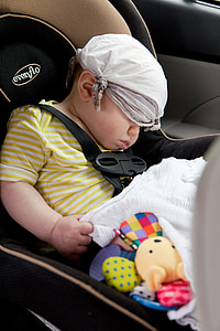 baby wearing yellow and white striped shirt sleeping on brown and black Evenflo booster seat inside car with white handkerchief covered on eyes and hair