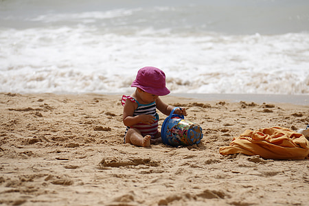 baby wearing purple hat playing sand near ocean at daytime